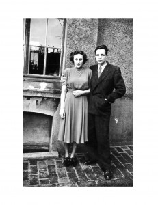 a young couple posing in front of a house
