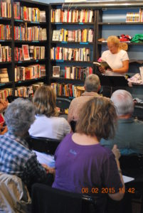 woman in bookstore reading in front of audience