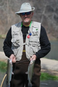 Man with two trout standing in stream