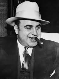 black and white photo of Al Capone in white hat and with cigar