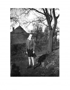 a young girl standing in a garden with a bunker behind her