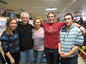 Shows a family of five in a bowling alley