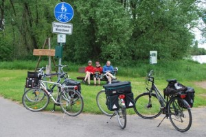 Three bicyclists taking a break during a bike trip