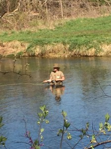 Woman fly-fishing in stream