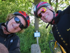 Two bicyclists at a sign marker