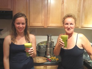 Two women with juice and juicer