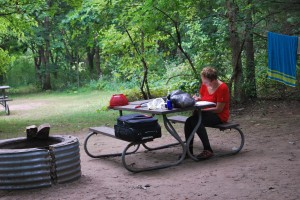 woman sitting at picnic table writing