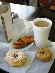 Styrofoam cup with coffee and two doughnuts