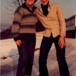 two teens standing in the snow in front of a building