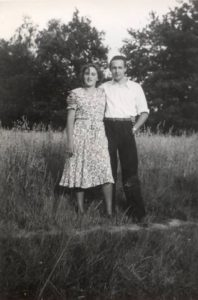 a young couple standing in a field