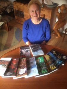 A middle aged woman with books on a table