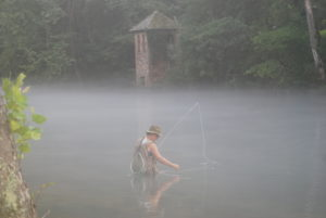 woman flyfishing fog