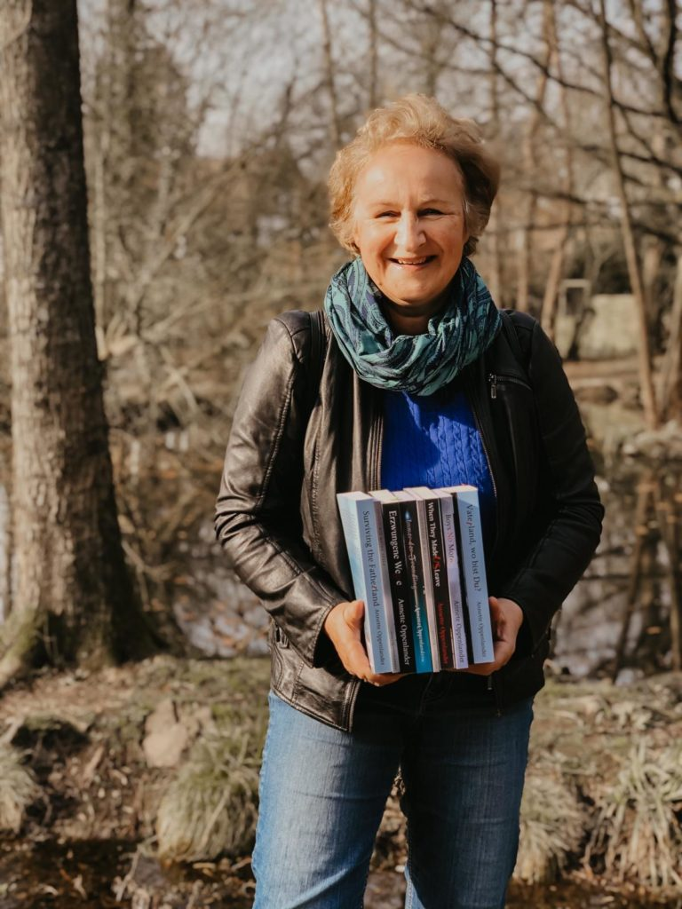 woman holding book in front of German bunker outside