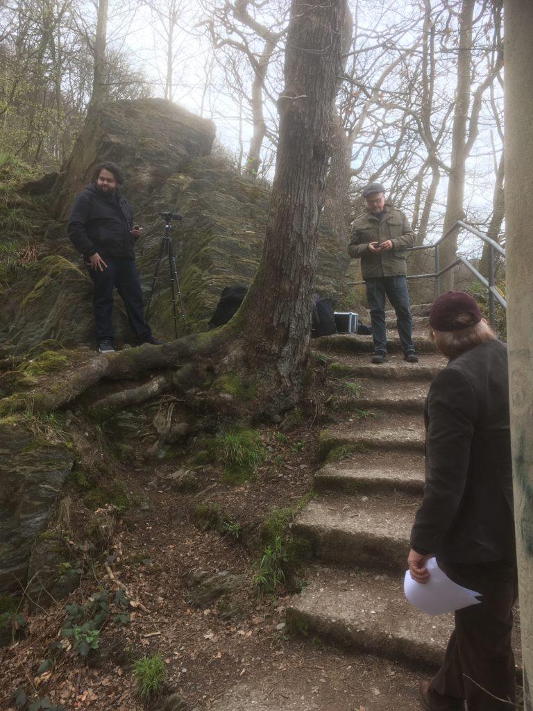 drei Männer bereiten Lesung im Wald vor