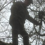 man sets up camera in woods