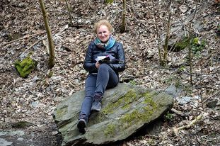 woman sits on rock with book